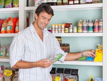 Man Selecting Food Packets In Store Stock Image