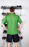 Man selecting footwear from the shoe rack mounted on wall. Vertical image of mature man, back towards camera, deciding which shoes to select from shoe rack royalty free stock images