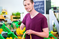 Man selecting fruits in corner shop. Man selecting bananas while grocery shopping in organic supermarket Royalty Free Stock Photos
