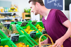 Man selecting fruits in corner shop. Man selecting bananas while grocery shopping in organic supermarket Stock Photos