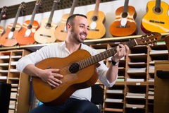 Man selecting guitar at studio Stock Image