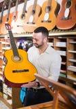 Man selecting guitar at studio Royalty Free Stock Photos