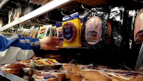 Man selecting ham in grocery store stock video footage