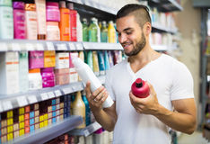 Man selecting shampoo in the store Stock Images