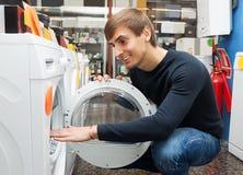 Man selecting washing machine. Handsome man selecting washing machine in hypermarket and smiling stock photos
