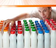 The man selects dairy products in the shop Stock Images