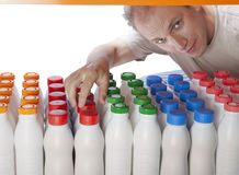 The man selects dairy products in the shop.  Stock Image