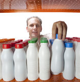 The man selects dairy products in the shop Stock Photo