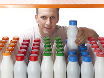 The man selects dairy products in the shop.  Stock Images
