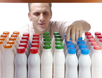 The man selects dairy products in the shop.  Royalty Free Stock Images