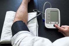 Man self-monitoring of blood pressure with a tensiometer Royalty Free Stock Image