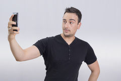 Man selfie. Man in black shirt taking a selfie with a cell phone making faces Royalty Free Stock Image