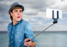 Man with selfie stick in front of sea. Digital composite of Man with selfie stick in front of sea Royalty Free Stock Photography