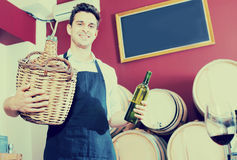 Man seller in apron holding big wicker bottle with wine Royalty Free Stock Photo