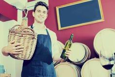 Man seller in apron holding big wicker bottle with wine. Cheerful man seller in apron holding big wicker bottle with wine in store Royalty Free Stock Photo