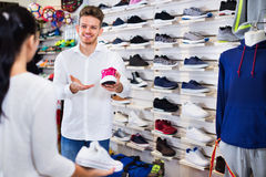 Man seller assisting girl in choosing sneakers Royalty Free Stock Photo