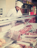 Man seller at the counter with meat Royalty Free Stock Photos