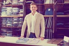 Man seller displaying diverse shirts. Young man seller displaying diverse shirts in men's cloths store Royalty Free Stock Image