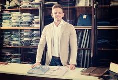 Man seller displaying diverse shirts. Young man seller displaying diverse shirts in men's cloths store Stock Photography