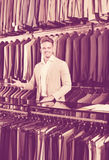 Man seller displaying diverse suits in men's cloths store Stock Photos