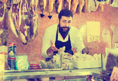 Man seller grouping meat to sell in butcher's shop Royalty Free Stock Photography