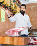 Man seller grouping meat to sell in butcher's shop. Smiling cheerful  man seller grouping meat to sell in butcher's shop Royalty Free Stock Photo