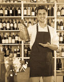 Man seller holding bottle of wine in shop. Friendly man seller in apron holding bottle of white wine in shop royalty free stock images