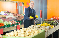 Man seller with lemon in vegetable shop Stock Photography