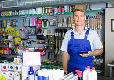 Man seller at pay desk in housewares store Stock Images