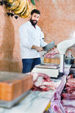 Man seller preparing meat to sell in butcher's shop. Smiling cheerful positive man seller preparing meat to sell in butcher's shop Stock Photo