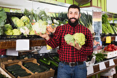 Man seller showing cauliflowers in grocery store. Smiling man seller showing cauliflowers in grocery store royalty free stock photography