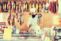 Man seller showing jamon Stock Photos
