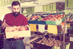 Man seller showing pomegranates in grocery store. Smiling man seller showing pomegranates in grocery store stock photo