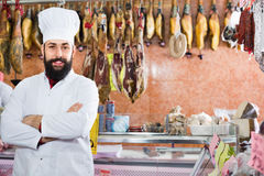 Man seller showing sorts of meat in butcher's shop Royalty Free Stock Photo