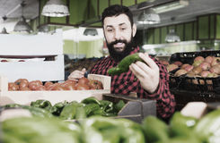 Man seller showing sweet peppers in grocery store. Smiling man seller showing sweet peppers in grocery store stock photo