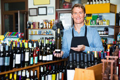 Man seller wearing apron having bottle of wine in hands. Friendly man seller wearing apron having bottle of wine in hands in wine house Stock Photos