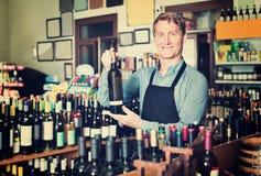 Man seller wearing apron having bottle of wine in hands. Glad positive friendly man seller wearing apron having bottle of wine in hands in wine house Royalty Free Stock Images