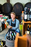 Man seller wearing apron having bottle of wine in hands. Positive man seller wearing apron having bottle of wine in hands in wine house Royalty Free Stock Image
