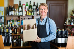 Man seller wearing apron having package box with wine bottles Stock Photos