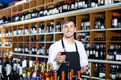 Man seller wearing uniform holding glass of wine Royalty Free Stock Image