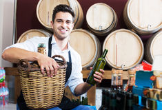 Man seller in wine shop. Glad man seller in apron having bottle of wine in shop with woods Royalty Free Stock Photography