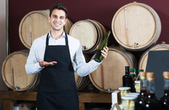 Man seller in wine shop. Positive man seller in apron having bottle of wine in shop with woods Royalty Free Stock Images