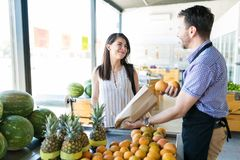 Man Selling Citrus Fruits To Woman In Store stock images