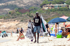 Man selling clothes in the beach. Santa Margherita di Pula, Italy - July 05, 2016: Black man selling clothes in Santa Margherita di Pula beach in Sardinia, Italy Royalty Free Stock Images