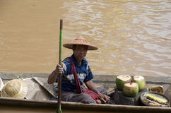 Man selling coconuts from canoe Stock Image