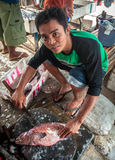 Man selling and cutting fish at a street market Royalty Free Stock Photo