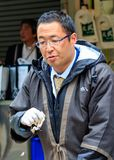 Man selling fish at the open air Tsukiji market in Tokyo - March 2015 stock image