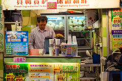 Man selling fresh juice and coconut drink at street shop. Hong K Stock Image