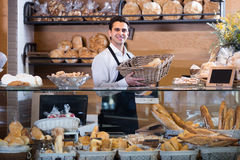 Man selling fresh pastry and baguettes Royalty Free Stock Photography
