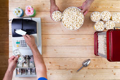 Man selling freshly made bowls of popcorn. Tendering money at the cash register for a customer, overhead view of their hands and the open till with American Royalty Free Stock Photography